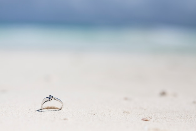 Close-up engagement ring in the sand