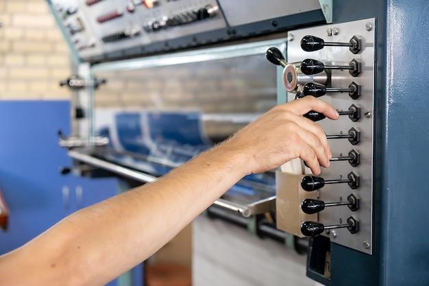 Cncマシンを制御するエンジニアの手の指を押すボタンを閉じる、倉庫で工場の機械を操作する労働者