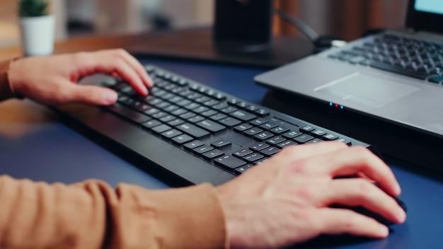 Primo piano delle mani dell'ingegnere che digitano sulla tastiera in ufficio a casa.