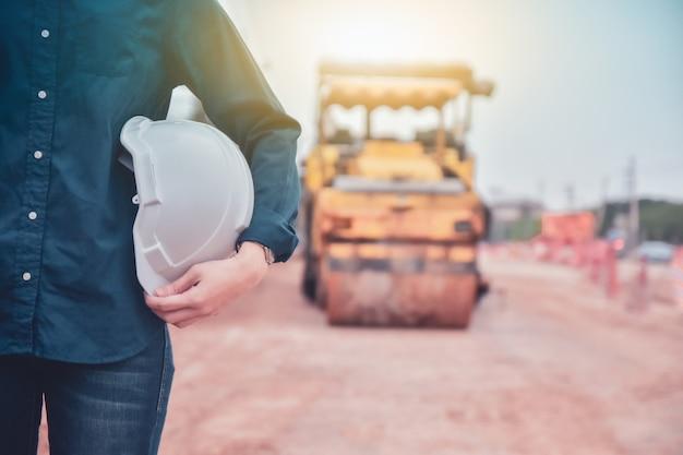도로 건설 배경에 서있는 하드 모자를 들고 엔지니어를 닫습니다