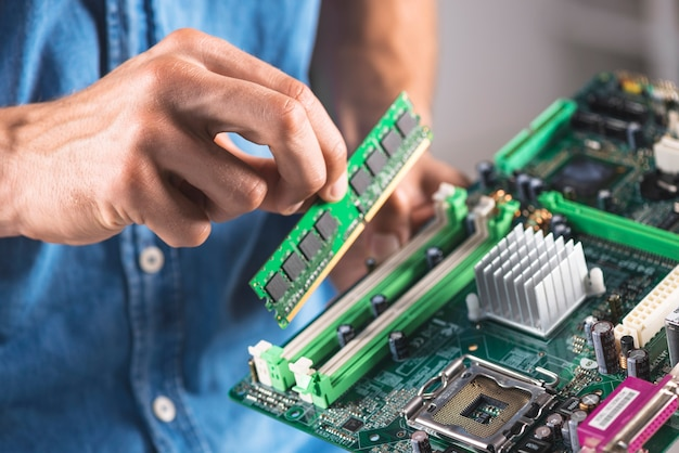 Close-up of engineer putting the ram memory module in computer motherboard