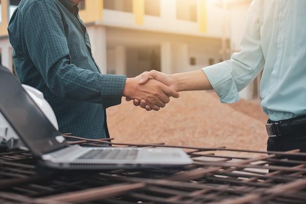 Крупным планом инженер пожимает руку на строительной площадке в концепции успеха совместной работы партнера