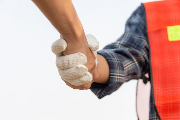Close up of engineer and worker handshake with blurred construction site, success and teamwork concept