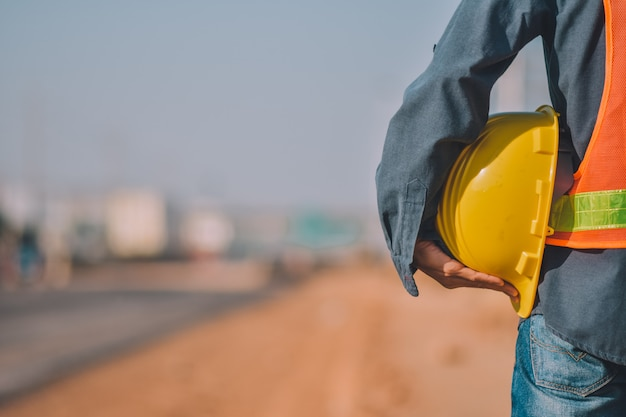 Close up engineering holding yellow helmet hard hat safety and road construction