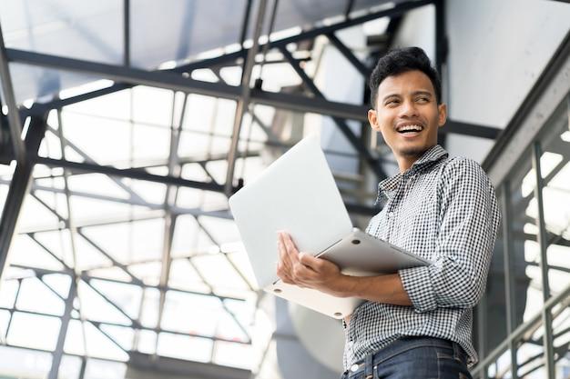 Закрыть инженер человека холдинг ноутбук и стоять над строительной площадки