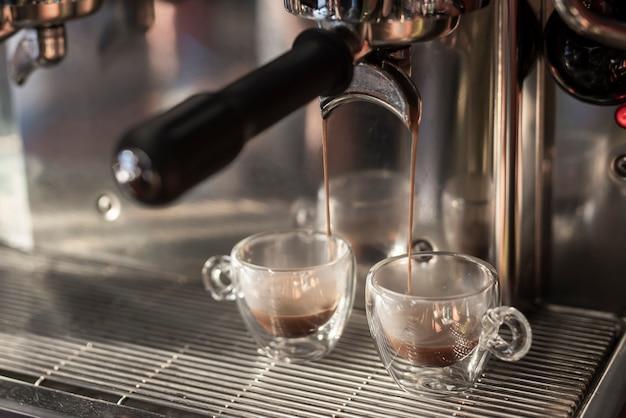 Close-up espresso pouring into cups