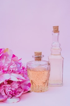 Close-up of essential oil bottles and flowers on purple backdrop