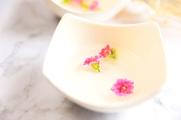 Close-up of essential oil with pink flower petals in bowl