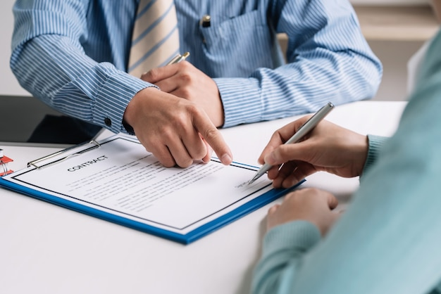 Close-up of estate agent hand pointing to the customer holding pen to sign a contract at the signing.