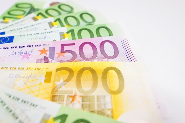 Close-up of euro banknotes on a white surface. the money is fanned out.
