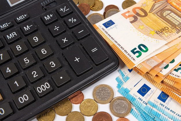 Close-up of euro currency coins, banknotes and calculator, finance planning concept