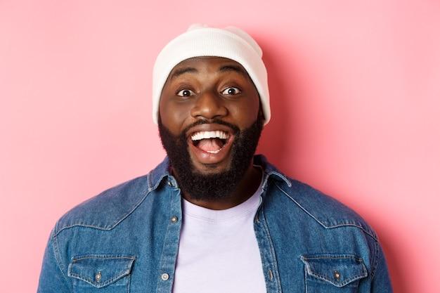 Primo piano del ragazzo afroamericano barbuto eccitato in berretto che fissa la telecamera, esprime stupore e gioia, in piedi su sfondo rosa