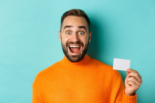 Close-up of excited caucasian man showing his credit card, smiling and staring amazed, standing in orange sweater against turquoise background