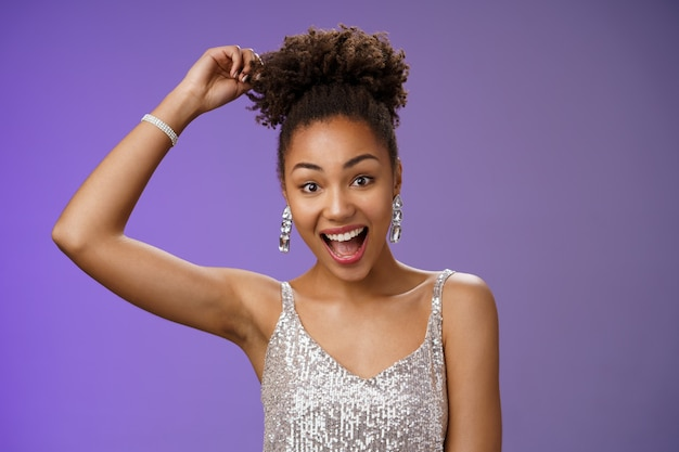 Close-up excited good-looking african-american curly-haired woman in trendy silver glittering dress touching afro curly smiling gladly having fun dancing amused standing entertained blue background.