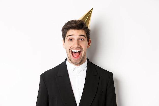 Primo piano di un bel ragazzo eccitato in abito alla moda e cappello da festa, che sembra stupito, che celebra le vacanze invernali, in piedi su sfondo bianco