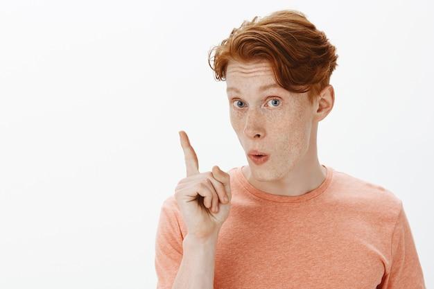 Primo piano dell'uomo rosso eccitato che dice suggerimento, alzando il dito come piano, trovato una soluzione