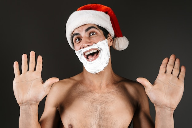 Close up of an excited shirtless man wearing santa claus hat standing isolated, with raised hands