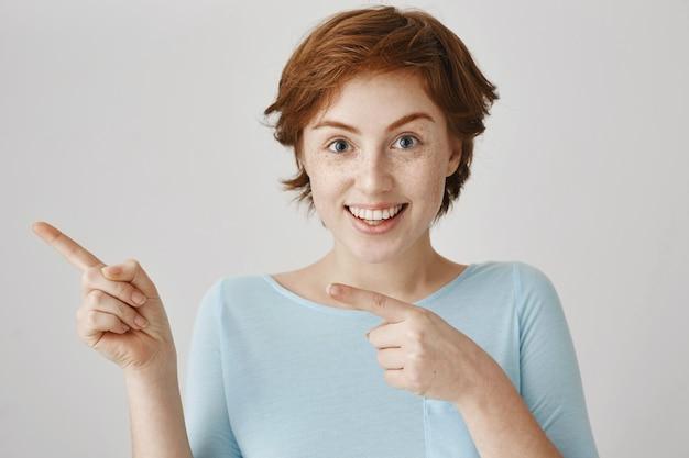 Primo piano della ragazza sciocca rossa sorpresa eccitata che indica le dita a sinistra