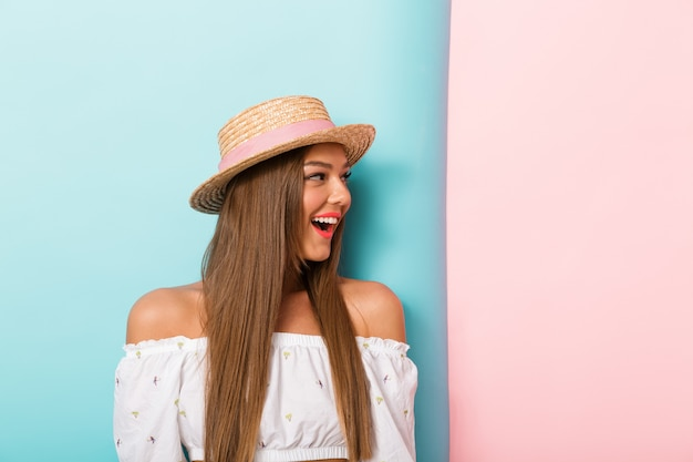 Close up of excited young woman in summer hat looking