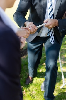 Close-up of executive with suit playing tug of war