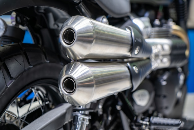 Close-up of exhaust or intake of black sport racing motorcycle with new tire and wheel in showroom. low angle photograph of motorcycle.