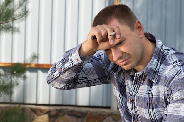 건설 현장에서 무언가를 생각하고 이마에 손을 대고 지친 남성 건축 계획자를 닫습니다