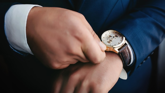 Close up of an expensive elegant watch. hands of wedding groom getting ready in suit.