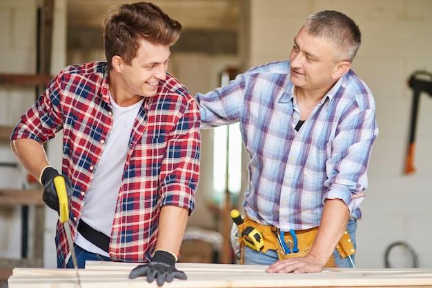 Primo piano sul falegname esperto e sul suo giovane impiegato