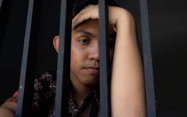 Close up expression of man holding bars in prison. looks sad and sorry. concept of corruption