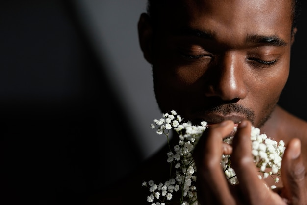 Крупным планом выразительный мужчина держит цветы