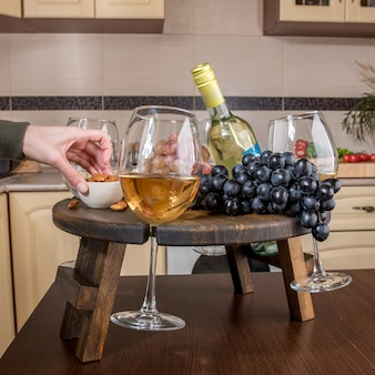 ぼやけたキッチンのワイングラスホルダーの拡張可能な木製トレイを閉じます