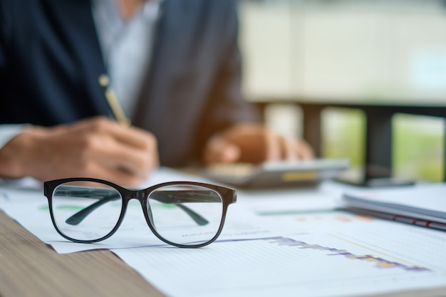 Close up eye glassess with businessman analysis maketing plan background