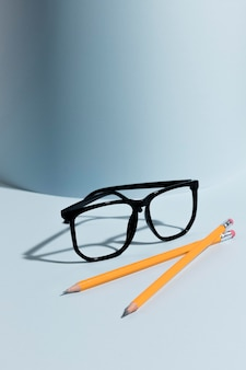 机の上のクローズアップの眼鏡と鉛筆