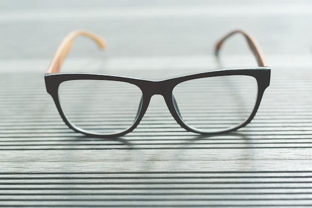 테이블 나무 색상 회색에 안경 패션을 닫습니다.