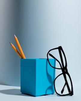 机の上の鉛筆とクローズアップの眼鏡