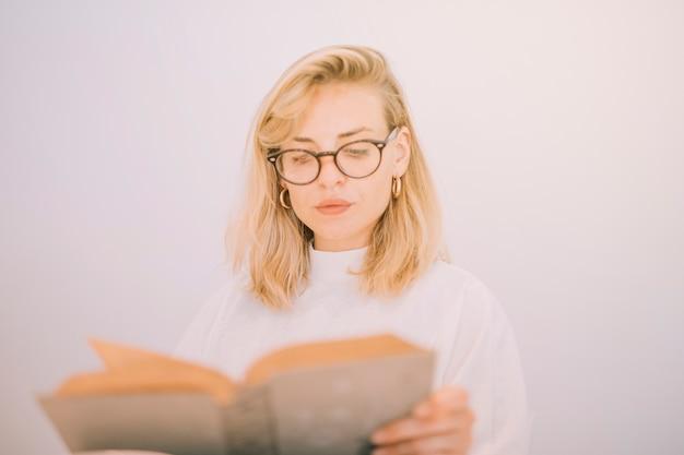 Close-up eyeglasses молодой женщины нося читая книгу изолированную на белом фоне