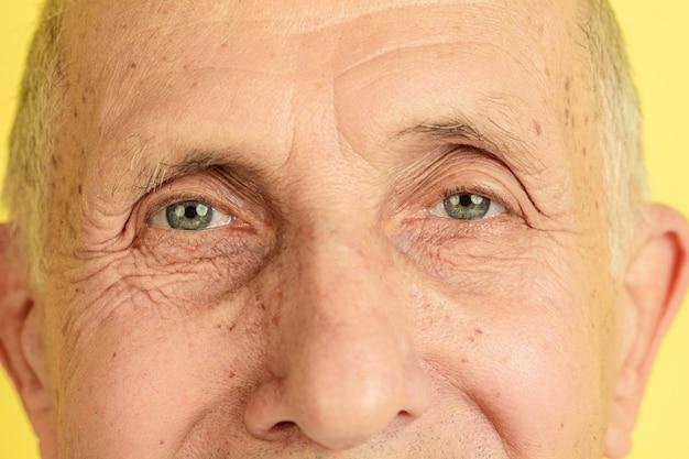 눈을 감 으세요. 노란색 스튜디오 배경에 고립 된 백인 수석 남자의 초상화. 아름다운 남성 감정 모델. 인간의 감정, 표정, 판매, 웰빙, 광고의 개념. copyspace.