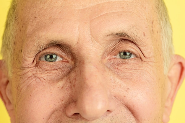 Close up, eyes. caucasian senior man's portrait isolated on yellow studio background. beautiful male emotional model. concept of human emotions, facial expression, sales, wellbeing, ad. copyspace.