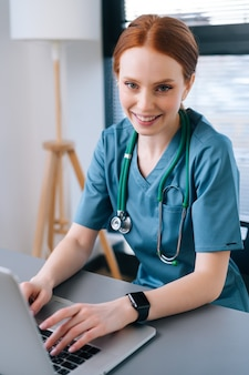 Close-up face of attractive smiling young female doctor in blue green medical uniform sitting at desk with laptop on background of window