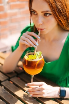 Close-up face of attractive young woman drinking cocktail through straw sitting at table in outdoor cafe in sunny summer day. beautiful female hipster student drinking cool lemonade through straw.