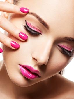 Fronte del primo piano di una bella ragazza con il trucco degli occhi rosa e unghie rosa brillante. modello di moda in posa sul muro bianco