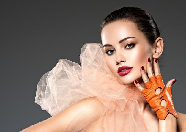 Fronte del primo piano di una bella donna con trucco marrone e unghie e labbra rosse. modello di moda in posa sul muro bianco