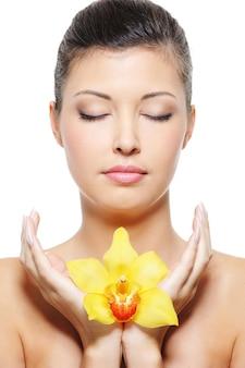 Fronte del primo piano di un rilassamento asiatico della donna di bellezza con il fiore nelle mani