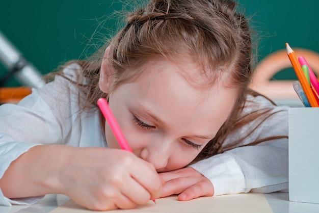 学校に初めてクラスで絵を描く顔の子供の女の子をクローズアップ
