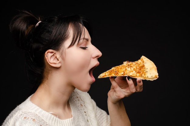 Close-up face of hungry young woman open mouth ready biting appetizing piece of pizza