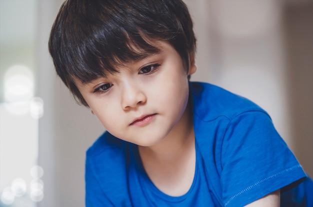 閉じる。顔の子供は笑顔で深い内面を探して、スナップショット健康な子自宅でリラックス、ハンサムな男の子がリビングルームで一人で遊んでいます。正の子供のコンセプト