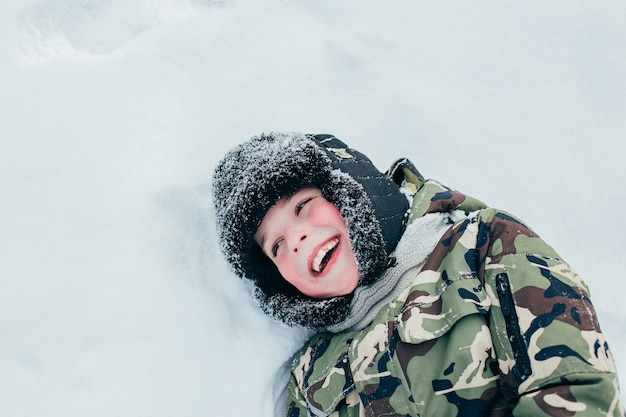 Close-up on the face of a laughing boy lying on the snow