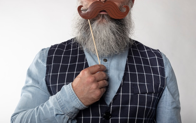 Close-up face of mature man with hipster beard and funny mustache with denim shirt