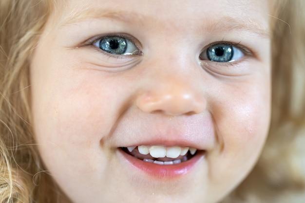 큰 파란 눈, 웃는 소녀를 가진 작은 귀여운 소녀의 얼굴을 닫습니다.