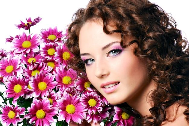 Крупным планом лицо молодой красивой женщины с цветами